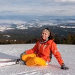 Young woman skier sitting on snow hill — Stock Photo