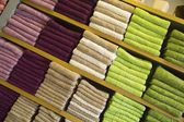 Multicolored Towels on a Wooden Shelves — Stock Photo