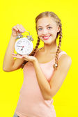 Beautiful young girl holding an alarm clock on yellow — Stock Photo
