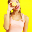 Young girl holding lemons on yellow background — Stock Photo #12414430