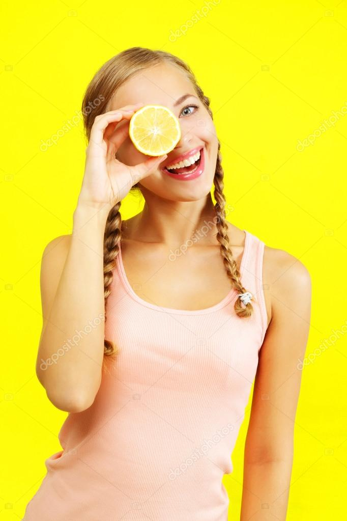 Young girl holding lemons on yellow background — Stock Photo #12414461