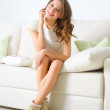 Smiling girl sitting on sofa — Stock Photo #16940549
