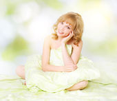 Beautiful girl sitting on a bed — Stock Photo