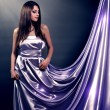 Beautiful girl in violet long dress on black background — Stock Photo #22892650