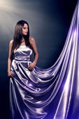 Beautiful girl in violet long dress on black background — Stock Photo