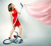Sexy girl using vacuum cleaner — Stock Photo
