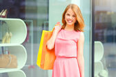 Smiling girl with shopping bags. Background windows — Stock Photo