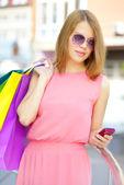 Niña sonriente con bolsas de compras — Foto de Stock