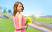 Smiling girl with yellow tulips — Stock Photo