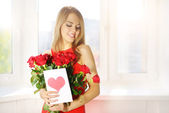 Beautiful girl with bouquet of red roses — Stock Photo