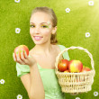 Attractive girl with a basket of apples — Stock Photo #38783517