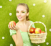 Attractive girl with a basket of apples — Stock fotografie