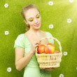 Attractive girl with a basket of apples — Stock Photo