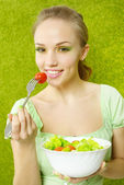 Smiling girl eating salad — Stock Photo