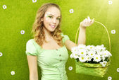 Smiling girl with a basket of flowers — Stock Photo