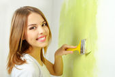 Beautiful girl painting a wall — Stock Photo
