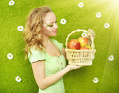Attractive girl with basket of apples — Stock Photo