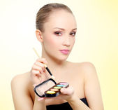 Attractive girl with makeup palette — Stock Photo