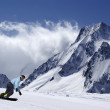 Stock Photo: Snowboarder on piste slope