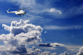 Helicopter in blue sky with clouds — Stock Photo