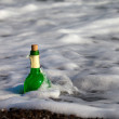 Bottle of wine in sea surf — Stock Photo