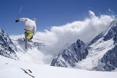 Freestyle ski jumper with crossed skis in high mountains — Stock Photo