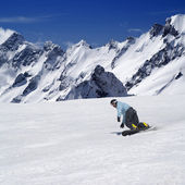 Snowboarder on ski piste in high mountains — Stok fotoğraf