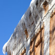 Snow-covered roof with icicles — Stock Photo