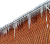 Snow-covered roof with icicles on white background — Stock Photo