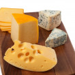 Different types of cheese on wooden board - Foto Stock