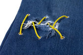 Blue jean with hole and crisscross yellow lacing — Stock Photo