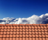 Roof tiles and sunny sky with clouds — Stock Photo