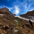 Stockfoto: Weary hiker ascent to mountain pass in evening