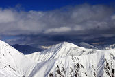 Snowy sunlit mountains and cloudy sky — Stock Photo