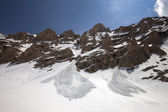 Snowy rocks and trace from avalanche — Stock Photo