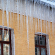 Stock Photo: Snow-covered roof with big icicles in winter day
