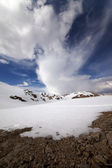 Snowy mountains and sky with clouds — Stock Photo