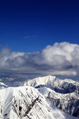 Winter snowy sunlit mountains and sky with clouds — Stock Photo