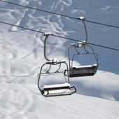 Two chair-lift with snowdrift in sun morning. Close-up view. — Stock Photo