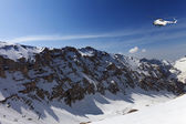 Helicopter in snowy sunny mountains — Stockfoto