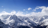 Panorama of snowy mountains in clouds — Stockfoto