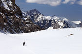 Hiker in snowy mountains — Stock Photo