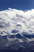 Winter mountains in evening and silhouette of paraglider — Stock Photo