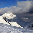 Off-piste slope and sunlit mountains in clouds — Stock Photo #37596603