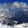 Sunlit winter mountains in clouds, view from off-piste slope — Stock Photo #38577399