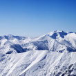 Snowy winter mountains and blue sky, view from ski slope — Stock Photo
