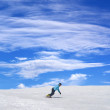 Stock Photo: Snowboarder on ski slope and blue sky with clouds