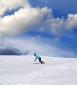 Snowboarder on ski slope and blue sky — Stock Photo
