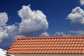 Roof tiles, snowy slope and blue sky with clouds — 图库照片