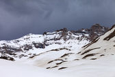 Snowy mountains and storm clouds — Photo